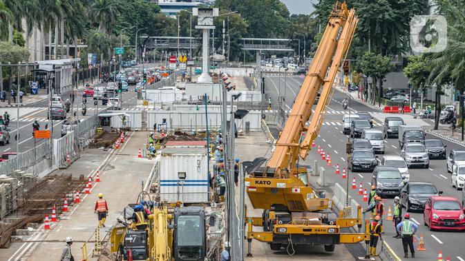 Pekerja mengoperasikan alat berat saat menggarap proyek MRT Fase II Bundaran HI-Harmoni di Jalan M.H. Thamrin, Jakarta, Rabu (10/2/2021) (Liputan6.com/Faizal Fanani)