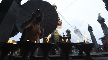 Umat Buddha berdoa di Stupa Swayambhunath pada acara Festival Buddha Purnima, selama lockdown virus corona yang diberlakukan pemerintah, di Kathmandu, Nepal, Rabu (26/5/2021). Waisak disebut juga Buddha Purnima atau Buddha Jayanti. (PRAKASH MATHEMA / AFP)