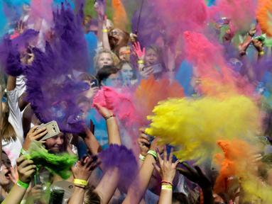 Puluhan peserta saling melemparkan bubuk warna selama mengikuti festival Holi di Riga, Latvia, (9/7). Festival ini selalu dirayakan setiap awal musim semi. (REUTERS/Ints Kalnins)