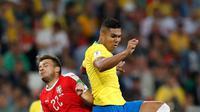 Gelandang Brasil, Casemiro berebut bola dengan pemain Serbia Adem Ljajic saat bertanding pada grup E Piala Dunia 2018 di Stadion Spartak di Moskow, Rusia (27/6). Brasil menang 2-0 atas Serbia dan melaju ke babak 16 besar. (AP Photo/Rebecca Blackwell)