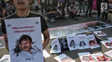 Sejumlah mahasiswa Trisakti melakukan aksi bertajuk #MerawatIngat #MenolakLupa saat car free day (CFD) di Bundaran HI, Jakarta, Minggu (5/5/2019). Aksi tersebut bertujuan untuk mengingatkan bahwa masih banyak kasus-kasus pelanggaran HAM berat yang belum terselesaikan. (Liputan6.com/Faizal Fanani)