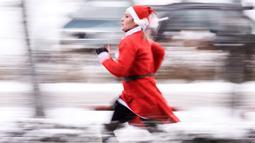 Seorang wanita berpakaian Sinterklas mengambil bagian dalam Santa Claus Run di Pristina, Kosovo, Minggu (16/12). Ratusan pelari berpartisipasi dalam lomba lari amal untuk menggalang dana bagi keluarga yang membutuhkan di Kosovo. (Armend NIMANI/AFP)