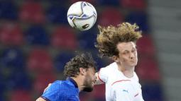 Pemain Italia, Manuel Locatelli, duel udara dengan pemain Republik Ceko, Alex Kral, pada laga uji coba di Stadion di Reanto Dall'Ara, Sabtu (5/6/2021). Italia menang dengan skor 4-0. (AP/Antonio Calanni)