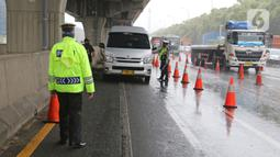 Petugas kepolisian memeriksa kendaraan yang melintasi Pos Penyekatan Jalur Mudik di Gerbang Tol Cikarang Barat, Kabupaten Bekasi, Senin (18/5). Memasuki H-6 Lebaran, puluhan kendaraan diminta untuk putar balik karena melanggar larangan mudik yang ditetapkan pemerintah. (Liputan6.com/Herman Zakharia)