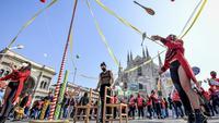 Seniman sirkus tampil di depan katedral gothic Duomo selama demonstrasi oleh pekerja sirkus di Milan, Italia utara (26/3/2021). Mereka menuntut lebih banyak dukungan dari pemerintah Italia karena kegiatan mereka ditutup sejak dimulainya wabah COVID-19. (Claudio Furlan/LaPresse via AP)