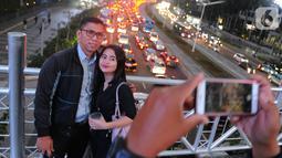 Warga berfoto di jembatan penyeberangan orang (JPO) yang tidak beratap di jalan Sudirman, Jakarta, Rabu (6/11/2019). Pemprov DKI mengklaim mayoritas masyarakat Jakarta setuju dengan konsep JPO terbuka dan tanpa atap yang kini dibangun di Sudirman. (merdeka.com/Arie Basuki)