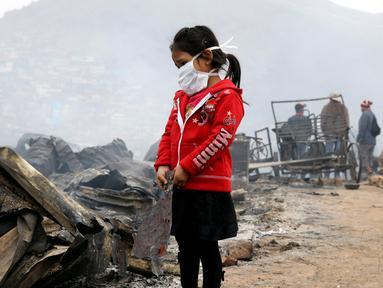 Seorang anak berdiri di lokasi kebakaran besar yang melanda permukiman Cantagallo di Lima, Peru, Jumat (4/11). Dilaporkan, permukiman yang terbakar itu dihuni oleh komunitas Suku Amazon yang tinggal di Lima. (REUTERS/Guadalupe Pardo)