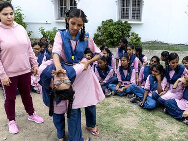 Dua siswi saat belajar bela diri di Telangana Minorities Residential Girls School di Hyderabad, India (17/6/2019). Maraknya kejahatan, kekerasan dan pelecehan seksual yang terjadi terhadap perempuan India membuat pelajaran bela diri diadakan di sekolah. (AFP Photo/Noah Seelam)