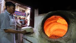 Tukang roti bersiap memasukkan adonan roti Iran atau taftoon ke dalam oven tradisional di sebuah toko di Kuwait City, Kuwait, 27 Juni 2019. Pembuat roti menaruh adonan di atas bantal untuk kemudian ditempelkannya ke dinding oven tradisional yang terbuat dari tanah liat. (YASSER AL-ZAYYAT/AFP)