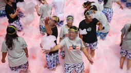 Sejumlah peserta bermain busa yang dicampur dengan air cabai selama acara di daerah Ningxiang di provinsi Hunan tengah, China (2/7/2019). Acara ini diadakan untuk menarik wisatawan ke daerah terebut yang terkenal dengan makanan pedasnya. (AFP Photo/STR)