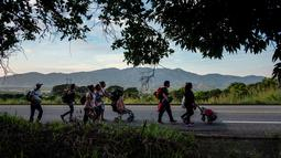 Imigran Honduras mendorong kereta bayi dalam perjalanannya menuju Amerika Serikat di Oaxaca, Meksiko, 29 Oktober 2018. Kereta dorong bayi tak hanya untuk balita mereka, tetapi juga dapat digunakan untuk membawa barang-barang. (Guillermo Arias/AFP)
