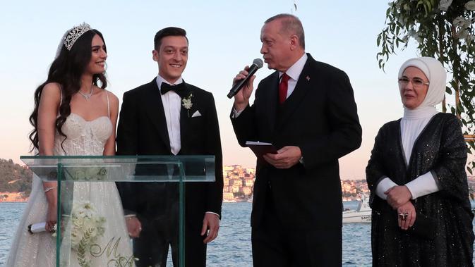 Presiden Turki Recep Tayyip Erdogan (kedua kanan) menghadiri pernikahan gelandang Arsenal asal Jerman, Mesut Ozil dan Amine Gulse di sebuah hotel mewah di Istanbul, Jumat (7/6/2019). Presiden Erdogan mendapat peran istimewa dengan menjadi pendamping Ozil. (TURKISH PRESIDENTIAL PRESS SERVICE/AFP)