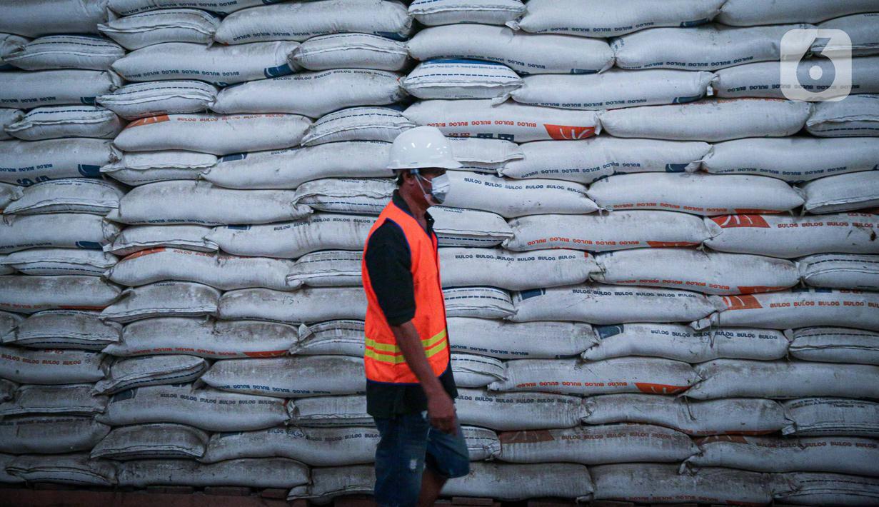 Pekerja melintas di depan tumpukan beras milik Perum Bulog di kawasan Pulo Mas, Jakarta, Kamis (26/11/2020). Kementan kembali memastikan bahwa meski tengah dilanda pandemi Covid-19 pasokan beras hingga akhir tahun masih ada stok beras sebanyak 7,1 juta ton. (Liputan6.com/Faizal Fanani)