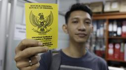 Seorang wartawan menunjukan sertifikat vaksin usai disuntik polio jelang SEA Games 2019 di Kantor Kemenpora, Jakarta, Rabu (13/11). Suntik vaksin tersebut untuk mengantisipasi wabah polio di Filipina. (Bola.com/M Iqbal Ichsan)