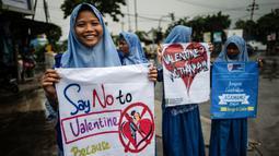 Seorang pelajar membawa spanduk saat menggelar demonstrasi menolak perayaan Hari Valentine di Surabaya, Jawa Timur, Kamis (14/2). Pelajar menilai Valentine sebagai pengaruh budaya asing. (Juni Kriswanto/AFP)