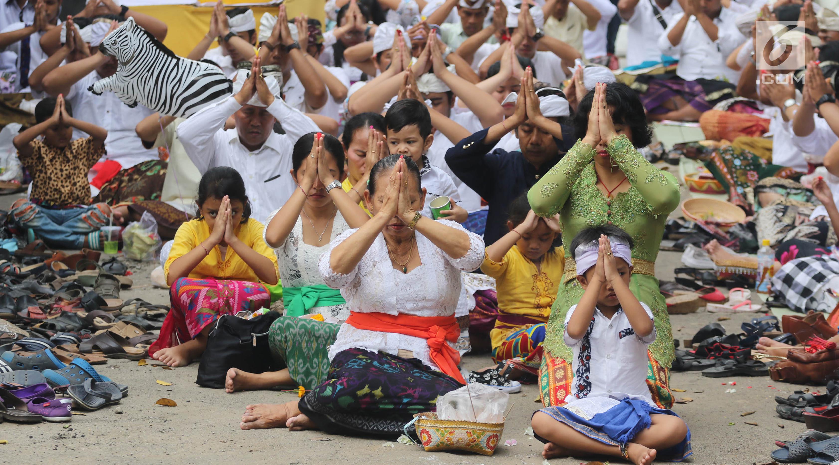 Sejumlah umat Hindu sembahyang saat upacara Tawur Kesanga di Pura Aditya Jaya, Rawamangun, Jakarta, Jumat (16/3). Upacara ini sekaligus menciptakan keseimbangan antara buana alit (manusia) dan buana agung (alam semesta). (Liputan6.com/Arya Manggala)