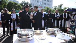 Pendeta usai memberi perjamuan pada jemaat GKI Yasmin dan HKBP Filadelfia pada misa Natal 2017 di Silang Barat Laut Monas, Jakarta, Senin (25/12). Dipimpin 16 pendeta dari beragam gereja, mereka menggelar kebaktian Natal. (Liputan6.com/Helmi Fithriansyah)