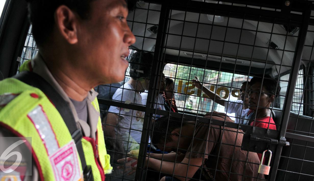 Tujuh warga yang diduga bandar narkoba dan terlibat dalam pengeroyokan digelandang petugas Kepolisian Polres Metro Jaktim untuk dilakukan pemeriksaan lebih lanjut, Kamis (21/1). (Liputan6.com/Yoppy Renato)