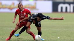 Gelandang Persija Jakarta, Riko Simanjuntak, berebut bola dengan gelandang PSIS Semarang, Septian David, pada laga Liga 1 di Stadion Patriot, Bekasi, Minggu (15/9). Persija menang 2-1 atas PSIS. (Bola.com/M Iqbal Ichsan)
