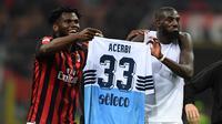 Dua gelandang AC Milan, Franck Kessie dan Tiemoue Bakayoko, mengarak jersey milik Francesco Acerbi selepas duel melawan Lazio di San Siro, Sabtu (13/4/2019). (AFP/Miguel Medina)