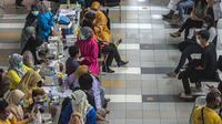 Warga menunggu untuk menerima dosis vaksin virus corona COVID-19 Sinovac di sebuah mal di Surabaya, Jawa Timur, Kamis (23/9/2021). Vaksinasi COVID-19 di Surabaya dilakukan di fasilitas kesehatan, mal, perkantoran, kelurahan hingga balai RW. (Juni Kriswanto/AFP)
