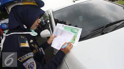Petugas mendata mobil peserta saat tes uji SIM dan kir transportasi online di Jakarta, Senin (15/8). Kegiatan diadakan menyambut HUT Kemerdekaan RI ke-71 serta menciptakan layanan angkutan umum yang prima dan accountable. (Liputan6.com/Immanuel Antonius)