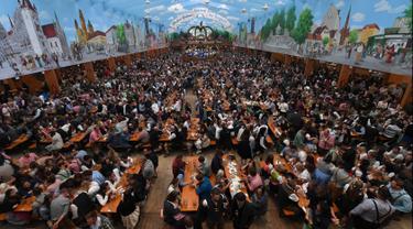 Pengunjung menikmati bir selama Festival Oktoberfest 2019 di sebuah tenda di Munich, Jerman selatan (3/10/2019). Festival bir terbesar di dunia Oktoberfest berlangsung hingga 6 Oktober 2019. (AFP Photo/Christof Stache)