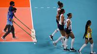 Relawan membersihkan lapangan saat babak penyisihan bola voli putri Olimpiade Tokyo 2020 antara Serbia dan Republik Dominika di Ariake Arena pada 25 Juli 2021. Relawan atau volunteer merupakan salah satu kunci suksesnya suatu perhelatan, tak terkecuali Olimpiade Tokyo 2020 ini. (YURI CORTEZ/AFP)