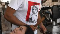 Dalam gambar pada 8 April 2021, tukang cukur Pakistan Ali Abbas menggunakan palu dan pisau daging untuk memotong rambut pelanggan di tokonya di Lahore. Berharap membuktikan kemampuannya dalam persaingan, Ali Abbas mengandalkan berbagai alat yang tidak biasa untuk melatih keahliannya. (Arif ALI/AFP)