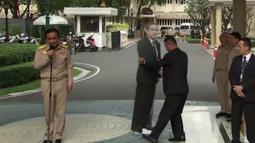 PM Thailand, Prayuth Chan-o-cha dalam konferensi pers saat pengawalnya memasang replika karton bergambar dirinya di Bangkok, Senin (8/1). PM Prayuth meminta para wartawan untuk mengajukan pertanyaan kepada replika karton dirinya tersebut. (TPBS via AP)
