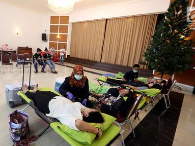 Petugas muslim dari Palang Merah Indonesia (PMI) membantu Jemaat Gereja Protestan Indonesia Bagian Barat (GPIB) dalam donor darah, Jakarta, Minggu (3/12). Kegiatan tersebut diadakan dalam rangkaian acara Natal. (Liputan6.com/JohanTallo)