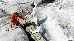 Anggota tentara Swiss memeriksa bagian pesawat tempur Perang Dunia II milik AS saat ditemukan di Gauli Glacier, di Bernese Alps, Swiss (17/9). Pesawat Perang Dunia II C-53 Skytrooper Dakota tersebut jatuh tahun 1946. (Peter Klaunzer/Keystone via AP)