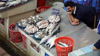 Seorang penjual menunggu pelanggan selama pelelangan di pasar ikan di Kuwait City (8/8/2021). Pelelangan dibuka kembali di negara itu setelah enam bulan ditutup di tengah pandemi virus corona. (AFP/ Yasser Al-Zayyat)
