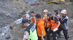 Petugas mengevakuasi korban tanah longsor di Magelang, Senin (18/12). Menurut pejabat setempat, delapan penambang tewas akibat longsor di lereng gunung berapi di pulau Jawa. (AFP Photo)