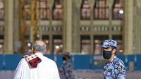 "Petugas keamanan Saudi berjaga-jaga saat orang Saudi dan ekspatriat melakukan sholat ""Al Fajr"" di Masjidil Haram di kota suci Mekkah (18/10/2020). Saudi juga memperbolehkan umrah untuk menampung 15.000 jamaah karena melonggarkan pembatasan virus corona. (AFP/STR)"