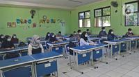 Sejumlah siswa mengikuti kegiatan belajar tatap muka di SMP Negeri 2 Bekasi, Selasa (23/3/2021). Pemerintah Kota Bekasi mengizinkan sejumlah sekolah yang berada di Zona Hijau mengadakan pembelajaran tatap muka atau PTM dengan mengikuti pedoman protocol. (Liputan6.com/Herman Zakharia)