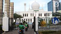 Pengendara motor antre mengambil takjil yang dibagikan dengan sistem drive thru di Masjid Agung Al-Azhar, Jakarta, Selasa (5/5/2020). Selama Ramadan, pengurus Masjid Agung Al-Azhar membagikan 300 takjil per hari buat pengendara yang melintasi lokasi tersebut. (Liputan6.com/Helmi Fithriansyah)