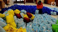 Petugas menata bansos berupa bahan pangan untuk didistribusikan kepada warga terpapar COVID-19 yang menjalani isolasi mandiri di rumah di Gedung Wanita, Kota Bogor, Jumat (9/7/2021). Setiap harinya, bonsos dibagikan kepada warga melalui keluarahan. (merdeka.com/Arie Basuki)
