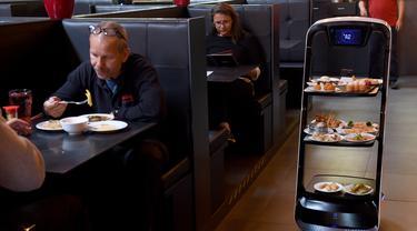 Robot mengantarkan makanan di restoran Asia di Wina, Austria, Kamis (28/5/2020). Restoran tersebut menggunakan robot untuk mengantar makanan guna mengurangi kontak yang tidak diperlukan antara pelayan dan pelanggan di tengah pandemi virus corona COVID-19. (Xinhua/Guo Chen)