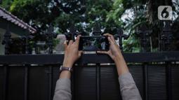 Seseorang mengambil gambar kondisi gedung sementara tempat para komisioner Komisi Pemilihan Umum (KPU) bekerja, tepat di sebelah Kantor KPU Pusat, Jakarta, Kamis (9/1/2020). Sebelumnya, Komisioner KPU Wahyu Setiawan ditangkap dalam OTT KPK pada Rabu 8 Januari 2020. (Liputan6.com/Faizal Fanani)