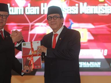 Yasonna Laoly (kanan) salam komando dengan Tjahjo Kumolo saat serah terima jabatan Menteri Hukum dan Hak Asasi Manusia (Menkumham) di Jakarta, Rabu (23/10/2019). Yasonna Laoly menggantikan Tjahjo Kumolo yang sebelumnya menjabat Plt Menkumham. (merdeka.com/Dwi Narwoko)