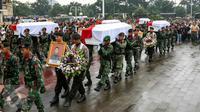 Sebanyak 13 jenazah korban jatuhnya helikopter di Poso dimakamkan TMP Kalibata, Jakarta, Selasa (22/3). Sebelumnya dilangsungkan upacara pelepasan jenazah yang dipimpin oleh Presiden Jokowi di Lanud Halim Perdana Kusuma. (Liputan6.com/Yoppy Renato)