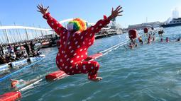 Seorang peserta dalam kostum Badut melompat ke dalam air pada kompetisi renang 'Copa Nadal' di Port Vell, Barcelona, Rabu (25/12/2019). Lebih dari 300 peserta menempuh jarak sejauh 200 meter pada tradisi lama yang digelar  saat hari Natal tersebut. (Josep LAGO / AFP)