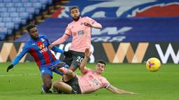 Gelandang Crystal Palace, Jeffrey Schlupp (kiri) melepaskan tendangan yang berbuah gol pertama timnya ke gawang Sheffield United dalam laga lanjutan Liga Inggris 2020/21 pekan ke-17 di Selhurst Park, Sabtu (2/1/2021). Crystal Palace menang 2-0 atas Sheffield United. (AFP/Catherine Ivill/Pool)