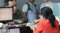 Petugas menghitung uang pecahan US$100 di Jakarta, Jumat (9/10/2015). Nilai tukar rupiah terhadap dolar AS pada perdagangan akhir pekan ini, Jumat (9/10/2015) mengalami penguatan, bahkan bergerak ke level Rp 13.400. (Liputan6.com/Angga Yuniar)