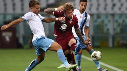 Penyerang Lazio, Ciro Immobile, berebut bola dengan pemain Torino pada laga lanjutan Serie A pekan ke-29 di Stadion Olimpico Grande Torino, Rabu (1/7/2020) dini hari WIB. Lazio menang 2-1 atas Torino. (AFP/Isabella Bonotto)