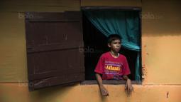 Pesepak bola SSB Tulehu Putra, Rizki Lestaluhu, saat berada di rumahnya di Tulehu, Maluku, Selasa (15/11/2017). Pekerjaan sang ayah sebagai pengendara ojek, membuat ekonomi keluarga Rizki tidak terlalu baik. (Bola.com/Vitalis Yogi Trisna)