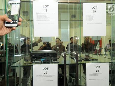 Sejumlah awak media mengabadikan deretan handphone (HP) berbagai jenis di intalasi yang akan dilelang di gedung KPK, Jakarta, Jumat (20/7). Handphone tersebut hasil sitaan KPK terhadap para koruptor yang ketangkap KPK. (Merdeka.com/Dwi Narwoko)