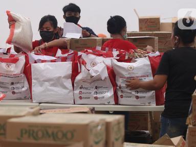 Pekerja sedang mengemas bantuan paket sembako dari Presiden Joko Widodo di Tangerang, Sabtu (9/6/2020).  Ribuan paket sembako tersebut akan didistribusikan kepada warga kurang mampu di wilayah Bodetabek guna mengurangi beban ekonomi mereka di tengah pandemi COVID-19. (Liputan6.com/Angga Yuniar)
