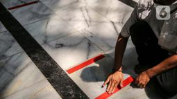 Petugas memasang tanda batas shaf di Masjid Cut Meutia, Jakarta, Kamis (30/7/2020). Masjid Cut Meutia akan menggelar Salat Idul Adha esok hari dengan menerapkan protokol kesehatan pencegahan Covid-19. (Liputan6.com/Faizal Fanani)